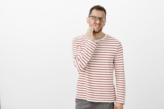 Innenporträt eines unzufriedenen unbequemen europäischen mannes in brille, der unter zahnschmerzen leidet