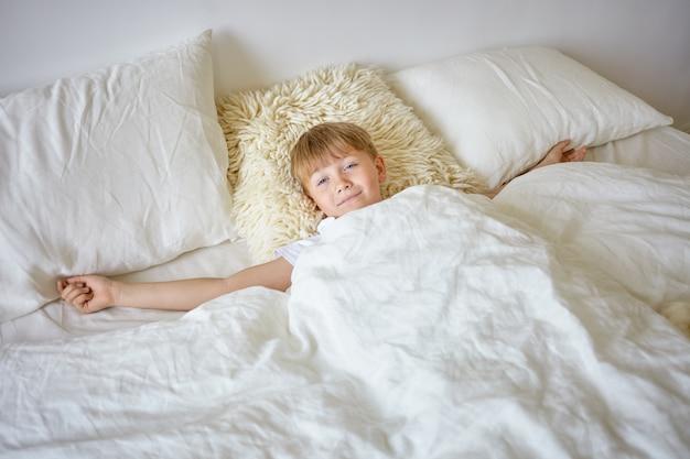 Innenporträt eines verschlafenen europäischen teenagers, der nach dem aufwachen am frühen morgen die arme ausdehnt, auf weißen bettdecken liegt, zur schule geht, schaut und einen faulen gesichtsausdruck hat