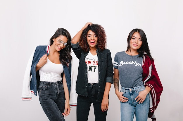 Innenporträt von drei aufgeregten studentinnen in trendigen kleidern, die nach dem unterricht gemeinsam spaß haben. lockiges mädchen in jeanskleidung, das zeit mit brünetten freunden verbringt und lacht.
