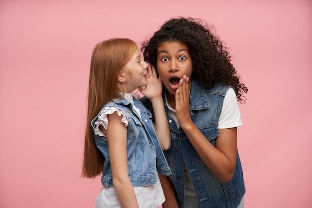 Innenporträt von jungen mädchen, die familienblick tragen, während sie auf rosa posieren, hände nahe ihren gesichtern halten, während sie überraschende nachrichten miteinander teilen