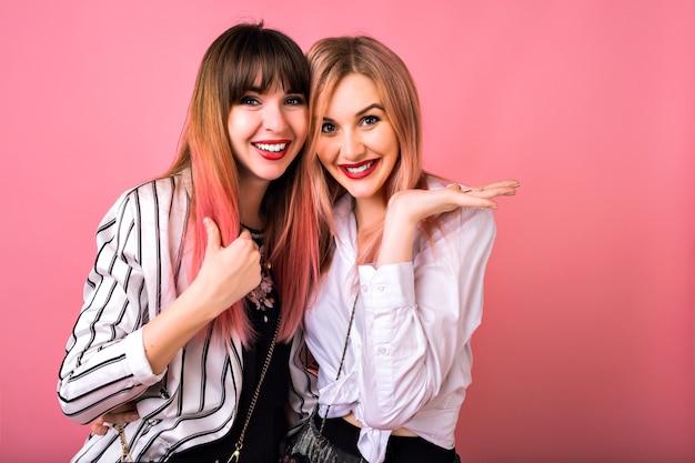 Innenporträt von zwei glücklichen besten freundinnen schwesternfrauen, die trendige schwarze und weiße kleidung und rosa haare, umarmungen und lächeln tragen, ausgelassene emotionen, hipster-stil