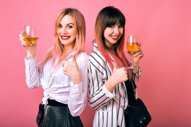 Innenporträt von zwei glücklichen schwestern der besten freundinnen, die trendige schwarze und weiße kleidung und rosa haare tragen, champagner trinken und gute wissenschaft zeigen, partyzeit