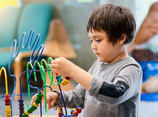 Innenporträtvorschuljunge, der im kinderclub mit weinleseton, das kind spielt spaß, das bunte spielwaren im kinderspielzimmer spielt. scherzen sie den jungen, der mit pädagogischen spielwaren im kindergarten spielt. bildungskonzept