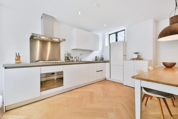 Innenraum der geräumigen küche mit weißen schränken und rostfreier dunstabzugshaube und schwarzer theke