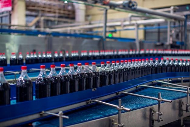 Innenraum der getränkefabrik. förderer, der mit flaschen für kohlensäurehaltiges wasser fließt.