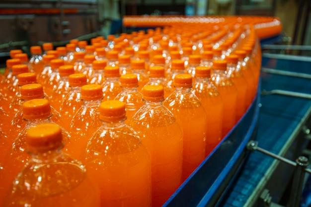 Innenraum der getränkefabrik. förderer, der mit flaschen für saft oder wasser fließt.