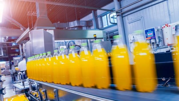 Innenraum der getränkefabrik. förderer mit flaschen für saft oder wasser. ausrüstungen