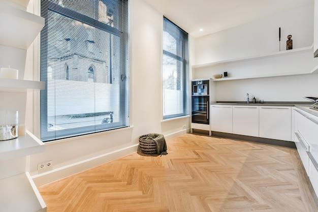 Innenraum der küche des hauses mit weißen minimalistischen schränken und eingebauten geräten und offenem durchgang zum esszimmer mit tisch