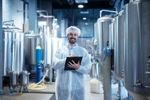 Innenraum der lebensmittelverarbeitungsanlage mit positiv lächelndem technologen, der checkliste hält