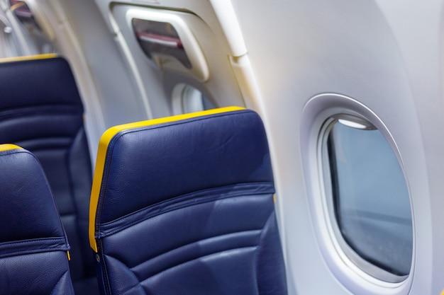 Innenraum der leeren flugzeugkabine. passagiere geben flugzeug frei. freier fensterplatz. annullierter flug, keine reise, fluggesellschaft stoppen niemand.