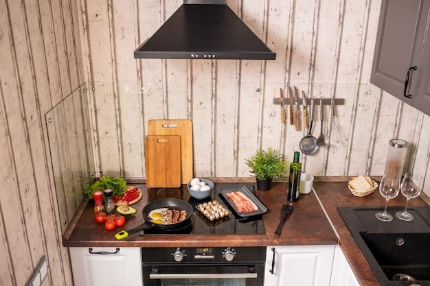 Innenraum der modernen küche mit elektroherd und tisch mit pfanne, lebensmittelzutaten, frischem gemüse, gewürzen und küchengeschirr