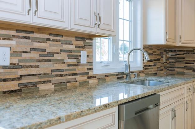 Innenraum der modernen küchengeräte auf herd, marmortheke mit weißen küchenschränken