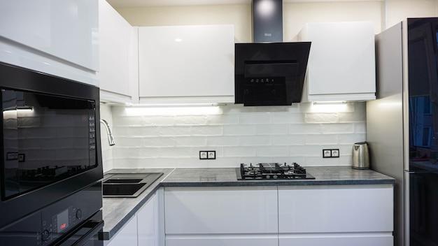 Innenraum der weißen möbel einer kompakten küche glänzende schränke mit eingebauten haushaltsgeräten