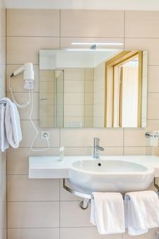 Innenraum des badezimmers im minimalistischen modernen stil mit spiegel, waschbecken auf steinständer, handtüchern und holzfliesen
