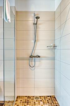 Innenraum des badezimmers im modernen minimalistischen stil mit dusche und transparentem glasschirm, handtuch und kleinen keramischen holzfliesen.