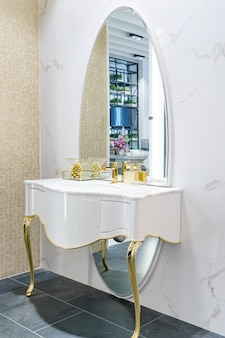 Innenraum des badezimmers mit waschbeckenhahn und weißem tuch.