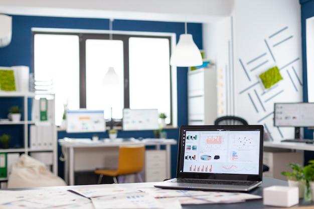 Innenraum des gemütlichen hellen firmenraums mit laptop, bereit zum brainstorming, moderne, stilvolle stühle, alle bereit für mitarbeiter. leeres, geräumiges büro mit kreativem arbeitsbereich.