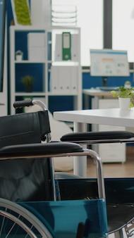Innenraum des gemütlichen hellen firmenraums mit rollstuhl, der in der nähe des schreibtisches und im leeren büroraum geparkt wird. moderne stilvolle stühle und desktop-computer, alles bereit für mitarbeiter, geräumiges büro für wirtschaftliches arbeiten
