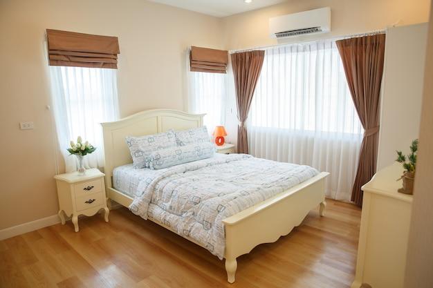 Innenraum des gemütlichen schlafzimmers im modernen design mit vase auf weißer hölzerner tabelle.