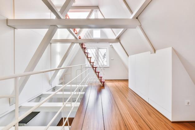 Innenraum des hellen dachbodens mit geländer und treppen gegen fenster im modernen haus