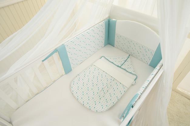 Innenraum des hellen gemütlichen babyraumes mit krippe und bettwäsche