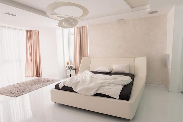 Innenraum des hellen schlafzimmers mit bequemem doppelbett, wecker auf kleinem tisch und grauem pelzteppich auf dem boden und beige vorhängen an den fenstern