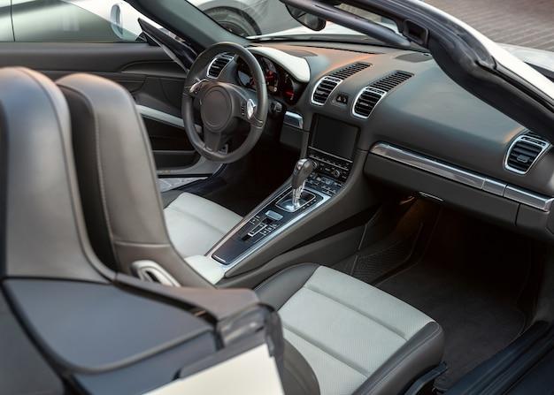Innenraum des luxus-cabrio-autos, blick von der beifahrertür. sportwagen-cabrio-interieur mit weißen sitzen und schwarzem armaturenbrett