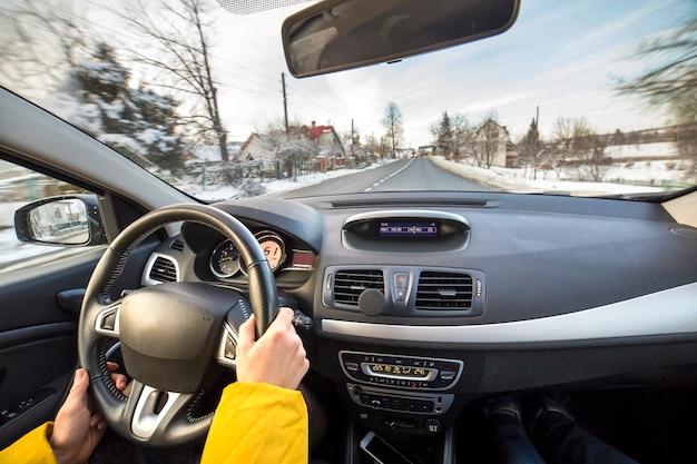Innenraum des modernen autos mit den weiblichen händen des fahrers am lenkrad, winterschneelandschaft draußen. sicheres fahrkonzept.