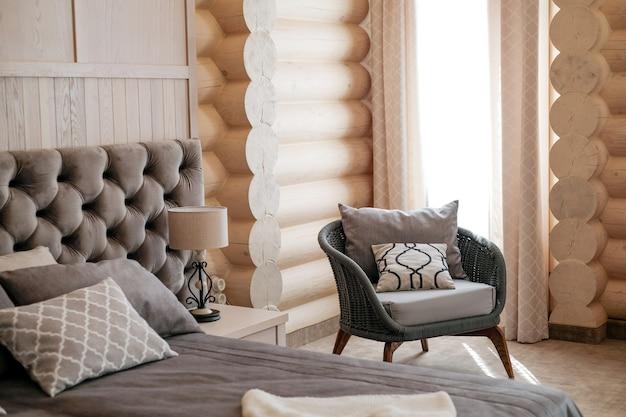 Innenraum des modernen hellen holzzimmers mit hohem fenster mit bequemem stuhl des vorhangs am sonnigen tag