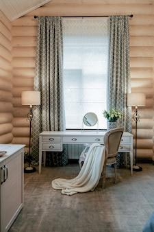 Innenraum des modernen hellen holzzimmers mit tischstuhl mit decke und lampe in der nähe des fensters