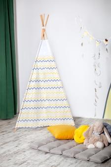 Innenraum des modernen kinderzimmers mit gelbem tipi. kinder wigwam nach hause. innenraum des stilvollen kinderzimmers mit spielzeug. skandinavischen stil. kinderzimmer mit einem wunderschön dekorierten spieltipi-zelt.