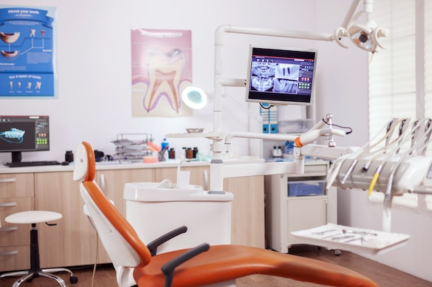Innenraum des modernen zahnarztkabinetts und des medizinischen stuhls. stomatologieschrank mit niemandem darin und orangefarbener ausrüstung für die orale behandlung.