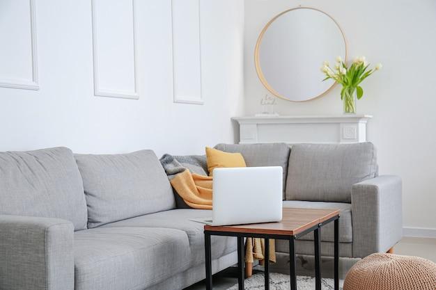 Innenraum des modernen zimmers mit bequemem sofa und kamin
