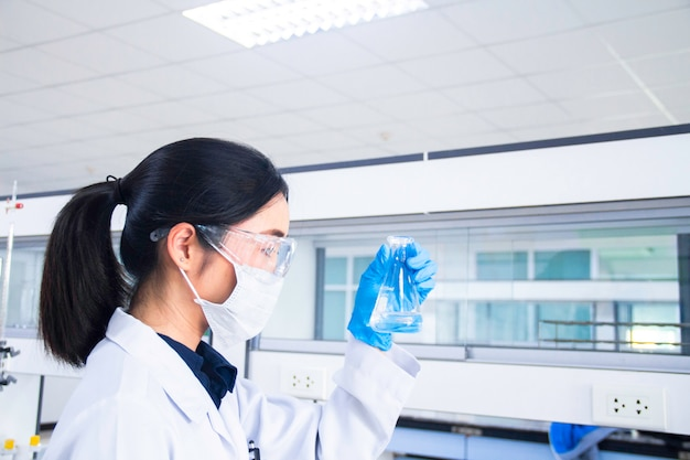 Innenraum des sauberen modernen medizinischen oder chemielabors. wissenschaftler, der an einem labor arbeitet. laborkonzept mit asiatischem frauenchemiker.