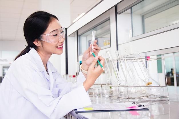 Innenraum des sauberen modernen weißen medizinischen oder chemischen labors laborwissenschaftler, der am labor mit reagenzgläsern und bericht arbeitet. laborkonzept mit asiatischem frauenchemiker.