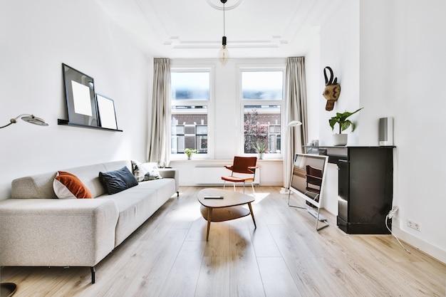 Innenraum des stilvollen hellen wohnzimmers mit modernen möbeln und fenstern in der wohnung