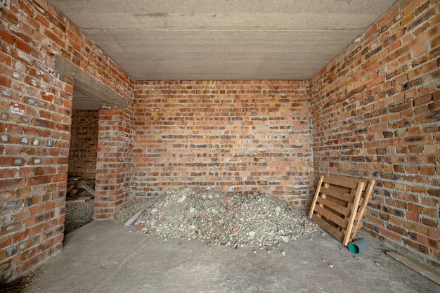 Innenraum des unfertigen backsteinhauses mit betonboden und kahlen wänden bereit zum verputzen im bau. immobilien-entwicklung