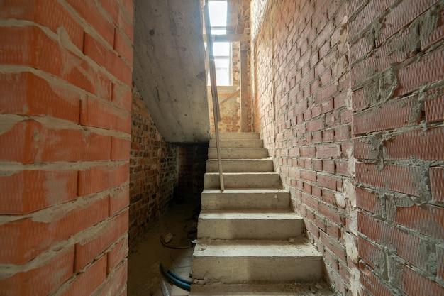 Innenraum des unfertigen backsteinhauses mit kahlen wänden, die zum verputzen bereit sind, und betontreppen, die feind keramikfliesenabdeckung vorbereitet.