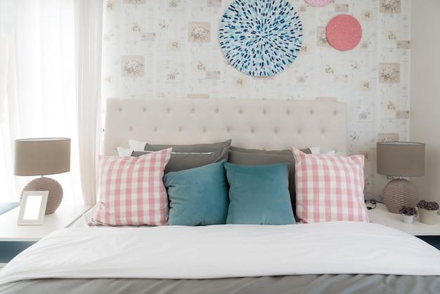 Innenraum des weißen schlafzimmers mit doppelbett und farbkissen zu hause.