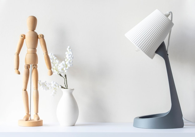 Innenraum des wohnzimmers. hölzerne schaufensterpuppe, vase mit dekorpflanze, lampe auf weißem holzschreibtisch, modell, minimale komposition, platz für text for