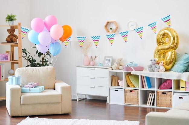 Innenraum des wohnzimmers in der modernen wohnung für geburtstagsfeier der kleinen kinder vorbereitet und mit luftballons und fahnen verziert