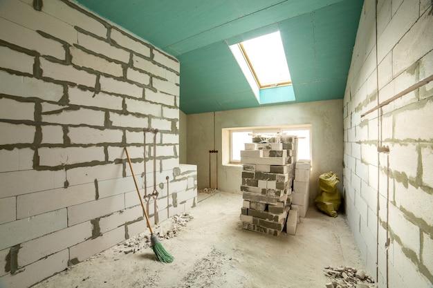 Innenraum eines apartmentzimmers mit nackten wänden und decke im bau.