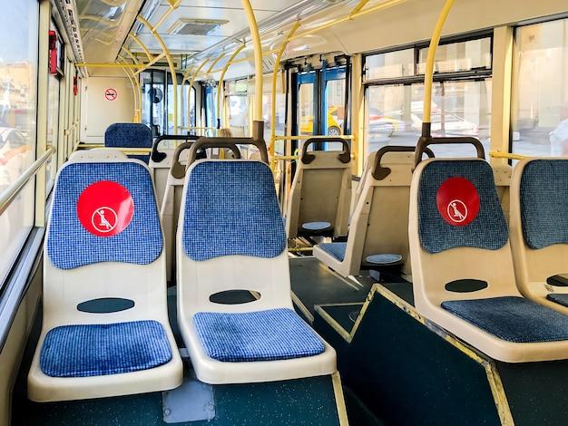 Innenraum eines leeren öffentlichen busses mit roten aufklebern auf den sitzen über die einhaltung der sozialen distanz