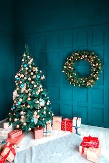 Innenraum eines schönen cyan-blauen raumes verziert für weihnachten, viele geschenkboxen und geschenke unter einem blauen tannenbaum und einem kranz