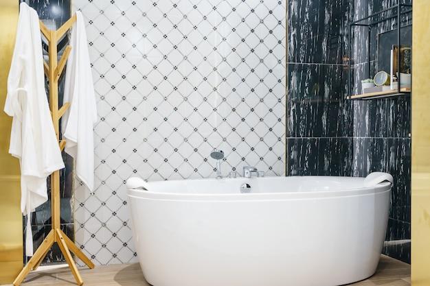 Innenraum eines zeitgenössischen badezimmerinnenraums mit einer weißen wanne und einer toilette