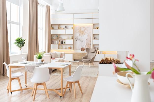 Innenraum geräumige helle wohnung im skandinavischen stil und warmen pastellweiß- und beigetönen. trendige möbel im wohnbereich und moderne details im küchenbereich.