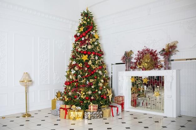 Innenraum im weißen raum mit dekoriertem neujahrsbaum, geschenkboxen und künstlichem kamin