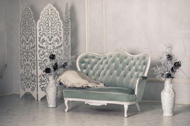 Innenraum mit weinlesemöbeln, helles frühlingsstudio mit schönem weißem sofa. weißer innenraum des studios.