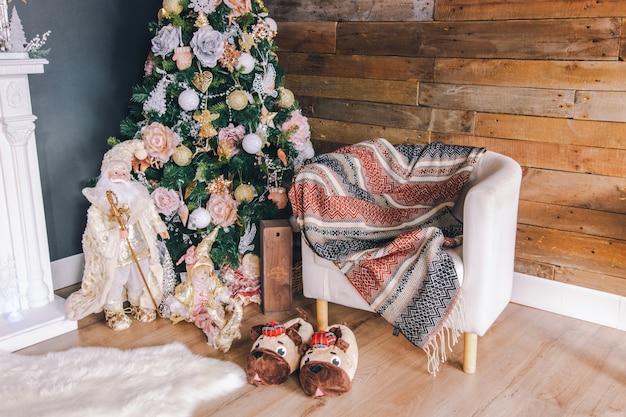 Innenraumdekor des neuen jahres oder des weihnachten: verzierter weihnachtsbaum, lehnsessel, pantoffel und teppich.
