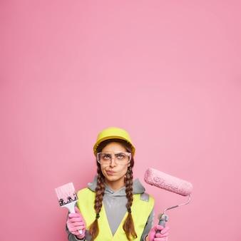 Innenrenovierung und heimwerken. ernsthafte unzufriedene frau, die in baukleidung gekleidet ist, hält reparaturwerkzeuge bereit, die oben zum bemalen von wänden einzeln über rosafarbenem wandkopierraum konzentriert sind